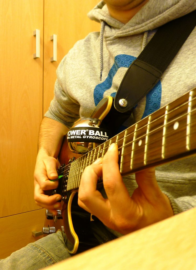 Man playing Guitar with Powerball to relieve RSI from guitar